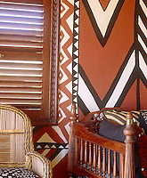 A living room inspired by traditional African motifs showing a detail of the walls which are entirely covered in dramatic abstract murals