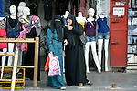 Women talk in front of a clothing store in the Zeitoun neighborhood of Gaza City, Gaza. Residents of the Palestinian territory are still reeling from the death and destruction of the 2014 war with Israel, and the continuing siege of the seaside territory by the Israeli military.