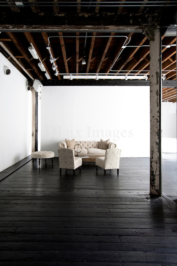 Living room in industrial space with exposed beams and wooden flooring