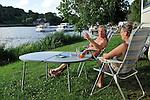 Campeurs à Chenillé-Changé (Maine et Loire) regardant la Mayenne et ses bateaux.