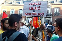 "Demonstrators  supports President Maduro holds a poster entitle ""Chavez not died, multiplied""."