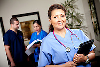 Ethnic Female Nurse with Colleagues in Background out of Focus