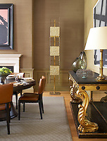 An antique console table with carved gilded legs furnishes one wall of this contemporary dining room