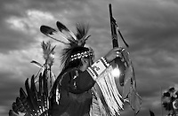 Men with a Pow wow traditional costume holding a rifle is dancing a war dance during the opening of the Veteran's Pow wow in Pine Ridge Indian Reservation. There is a deep warrior tradition among the Sioux. The Veterans POW wow honors veterans from World War II, Korea, Vietnam, the invasion of Panama and both U.S. wars against Iraq and Afghanistan.