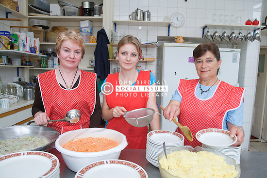 Cooks holding various kitchen utensils in kitchens of Polish Social Club,