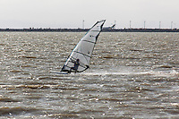 A windsurfer skims across the waters of San Francisco Bay near the Oakland International Airport.