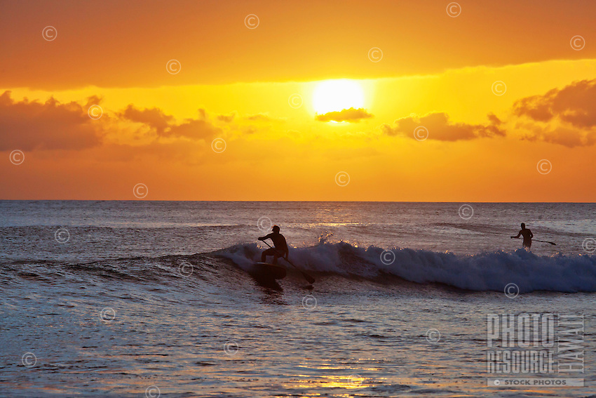 Standup paddlers make the most of the waves at sunset at Launiupoko Beach Park, Maui.