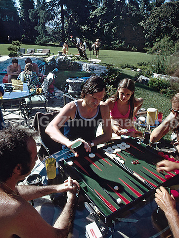 Hugh Hefner playing backgammon at the Playboy Mansion, Los Angeles, 1973. Photo by John G. Zimmerman.