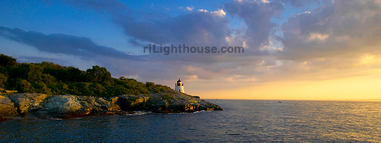 The sun sets over Castle Hill Lighthouse at the mouth of Narragansett Bay.