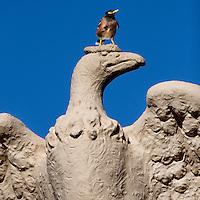 """Victorious"" mynah bird perched atopSculpture from the Waikiki War Memorial Natatorium,Oahu, Hawaii"