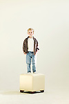 young boy standing on stool in white studio..Model released