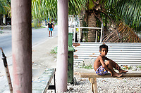 A young boy sits on a bench in the Tuvaluan capital of Funafuti. Located in the South West Pacific Ocean, Tuvalu is the world's 4th smallest country and is one of the most vulnerable to climate change impacts including sea level rise, drought and extreme weather events. Tuvalu - March, 2019.