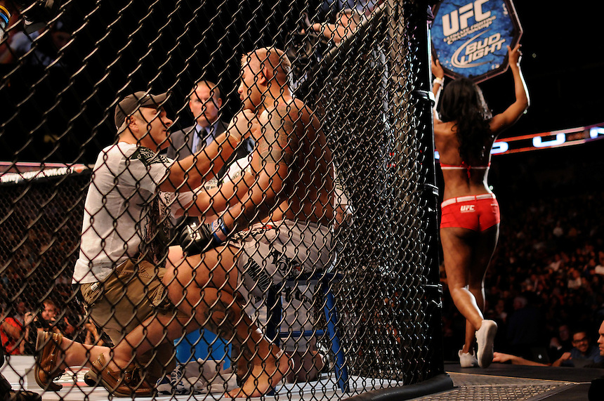 24 SEPTEMBER 2011:   Mark Hunt is tended to by trainers as an Octagon Girl rounds the ocrtagon  during UFC 135 at the Pepsi Center in Denver, Colorado. *****For Editorial Use Only*****