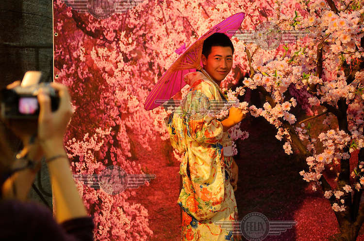 Showing pleasure in Japanese style, a visitor to an interactive art exhibition poses for photos in a provided kimono, in a gallery in 7-9-8 district. Also known as 'Dashanzi', this art zone consists of hundreds of galleries, studios and media businesses in former military factories in a Bauhaus-esque designed complex in the North West of the city