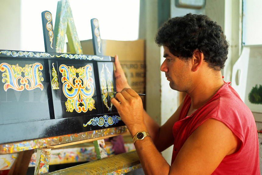 Costa Rican artist decoratively painting a wagon. Costa Rica, South America