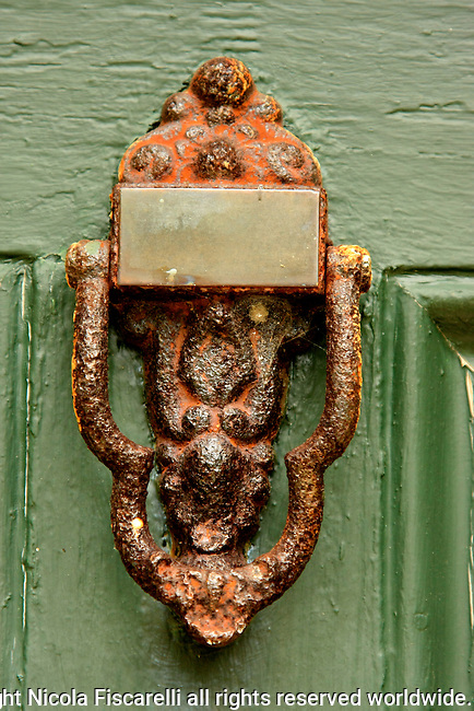 Antique  door knocker on the heavily painted green color entrance door.