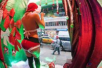 Maria, as Miss Santa, dances and greets passerby from the window of Vivid Cabaret in Midtown Manhattan in New York on Wednesday, December 10, 2014. The gentlemen's club is having their own live Santa display for the holidays and is giving out presents of free admission cards, no lumps of coal from Miss Santa. (© Richard B. Levine)