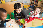 Education Preschool classroom scenes 4-5 year olds boys playing with dollhouse and toy plastic bears