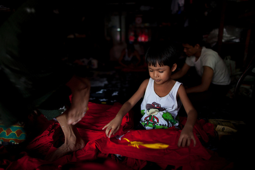 A boy helps sort through freshly made National League for Democracy (NLD) t-shirts at his family's silk screening shop ahead of the country's by elections, in Yangon, Myanmar, March 25, 2012.