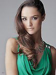 Beautiful brunette fashion model closeup in green dress