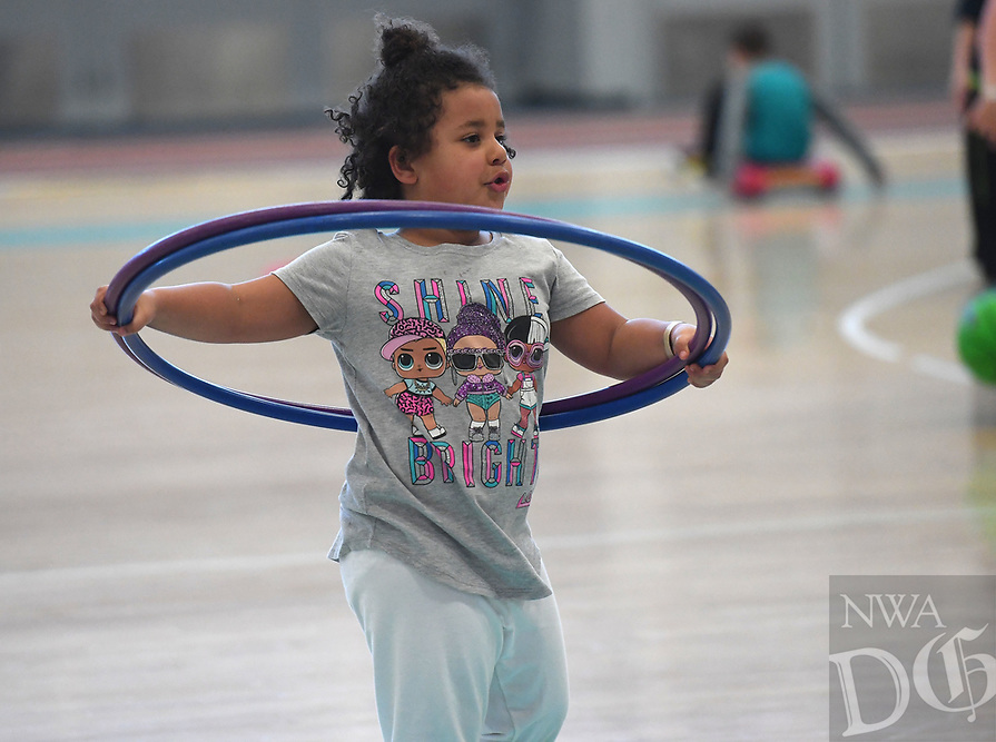 NWA Democrat-Gazette/J.T. WAMPLER Izzy Ochieng, 5, of Fayetteville plays with a hula-hoop Monday March 18, 2019 at the Jones Center in Springdale. The center is open all week for spring break with extended hours. The pool, gym and rink will be open all week with a special activity scheduled for each day through week. For information on activities at the Jones Center visit www.thejonescenter.net