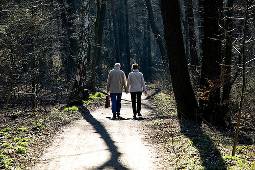 Older couple walking down a lane in early spring