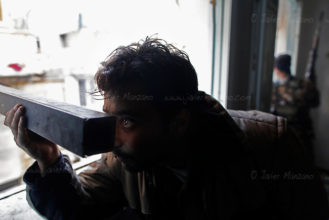 35-year-old Allam, a Kurdish Free Syria Army soldier belonging to the Liwa Salahadeen reviews the regime army positions through a home-made periscope at his base in the besieged neighborhood of Karmel Jabl. Aleppo, 12/06/2012..©Javier Manzano
