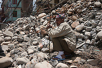 A man sits on his distorted house in Sindhupalchok, outskirt of Kathmandu, Nepal. May 1, 2015