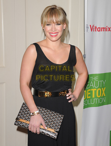 HILARY DUFF.at The The Beauty Detox Solution by Kimberly Snyder held at The London in West Hollywood, California, USA, .April 13th 2011..half length fringe  red lipstick make-up beauty black vest sleeveless dress belt gold clutch bag brown patterned hand on hip .CAP/RKE/DVS.©DVS/RockinExposures/Capital Pictures.