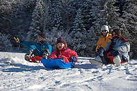 Three children sledding down a snowy hill while their mother looks on.