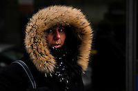 New York, United States. January 23, 2013. .A woman takes cover of the wind as she walks during a cold Temperature under zero in New York City  -- . Photo by Eduardo Munoz Alvarez / VIEWpress.