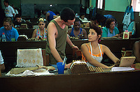 Workers talk while working at the Partagas cigar factory produce more than one hundred million cigars in a year--over 32,000 a day. Cuban cigars are coveted throughout the world because of their superior quality of tobacco. Each roller makes at least 105 cigars a day--they are paid more if they make more. They listen to a lector read a book to the workers to alleviate boredom.