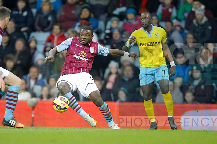 Jores Okore of Aston nVilla clears the ball ahead of Yannick Bolasie of Crystal Palace - Barclays Premiership Football - Aston Villa v Crystal Palace - Villa Park  Birmingham - Season 14/15 - 01/01/2015 <br /> Photo: Malcolm Couzens/Sportimage