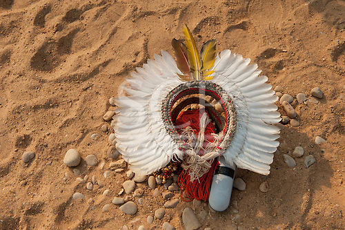 A white feather cokaa headdress lies on the ground with the owner's iPhone speaker at the International Indigenous Game, in Brazil. 30th October 2015