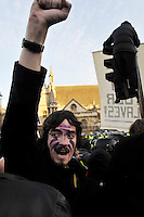 A protestor puts a fist in the air as another climbs on top of traffic lights during a student demonstration in Westminster, central London on the day the government passed a bill to increase university tuition fees.