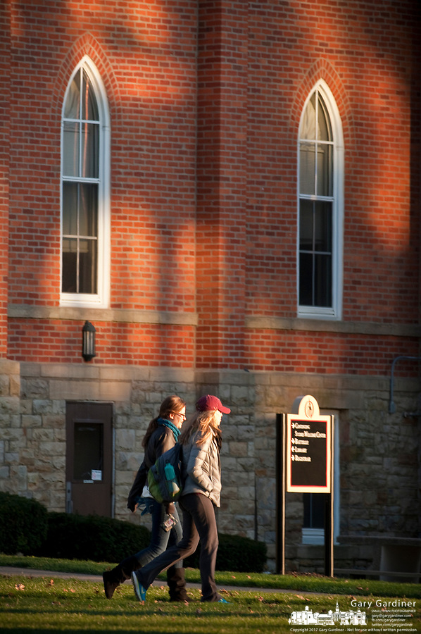 Otterbein students walk into the sun at sunset as they walk back to their homes after studying on campus in Westerville, Ohio.