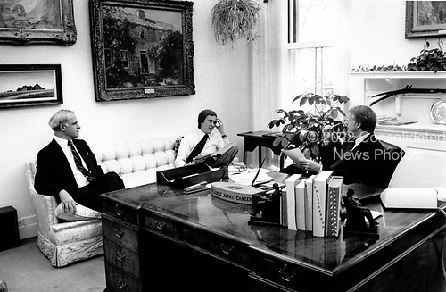 """United States President Jimmy Carter, right, chief speechwriter Jim Fallows, center, and US Secretary of Energy James R. Schlesinger, left, apply last-minute touches to the scheduled energy address to the nation on live television in the evening at the White House in Washington, DC on April 18, 1977.  In his remarks, the President will equate the energy crisis as the """"moral equivalent of war.""""<br /> Credit: White House via CNP"""