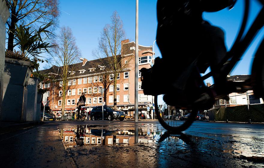 Nederland, Amsterdam, 30 jan 2013.Europaplein. Hier komt een metrostation voor de Noord-zuidlijn, ondergronds is het al gebouwd. De scheldestraat komt hier uit op het europaplein. Fietsers op het fietspad en spiegelingen in plassen op straat..Foto(c): Michiel Wijnbergh