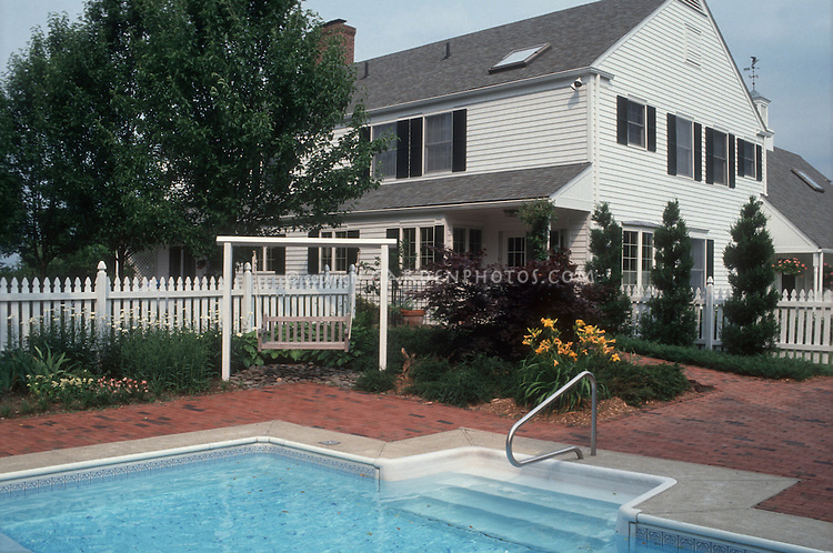 White picket fence with a purpose: Encircling the in-ground swimming pool, with flower garden landscaping, white Colonial style traditional house with black shutters and roof skylight, brick patio, daylilies, summer blue sky, blue water, garden bench swing, trees, flowers, perennials, evergreens, Japanese maple, pool steps, on a summer day