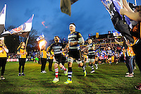 Francois Louw, mascot in hand, and the rest of the Bath Rugby team run out onto the field. Aviva Premiership match, between Bath Rugby and Saracens on April 1, 2016 at the Recreation Ground in Bath, England. Photo by: Patrick Khachfe / Onside Images