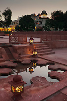 Lantern-side pools, illuminate the grounds at dusk in the intricate gardens surrounding Jaipur's Jai Mahal Palace Hotel.
