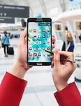 Woman hands with Samsung Galaxy Note III smartphone at airport