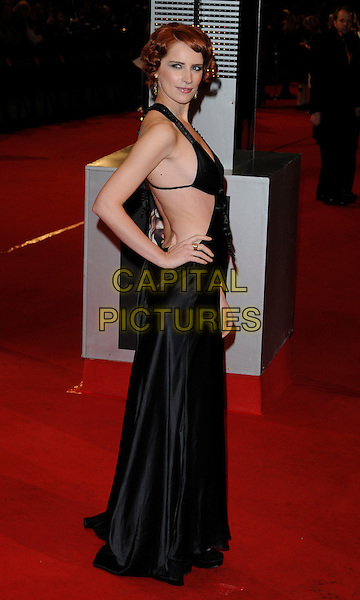 GUEST .Arrivals at the Orange British Academy Film Awards 2010 at the Royal Opera House, Covent Garden, London, England, UK, .21st February 2010.BAFTA BAFTAs full length black dress cut out away side long maxi silk satin dress hand on hip .CAP/CAN.©Can Nguyen/Capital Pictures