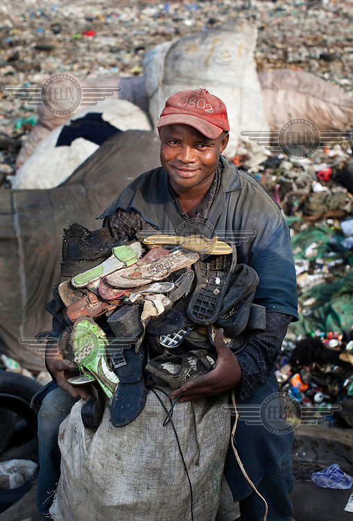 A man holds a pile of shoes and soles which he has found on the Olusosun rubbish dump in Lagos. The Olusosun dump is Nigeria's largest rubbish dump comprising over 100 acres of waste and is believed to be the largest in Africa. ..