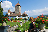 CHE, Schweiz, Kanton Bern, Berner Oberland, Spiez: Schloss Spiez am Thunersee - Frau sitzt auf Gelaender | CHE, Switzerland, Bern Canton, Bernese Oberland, Spiez: castle Spiez at Lake Thun - woman sitting on bench