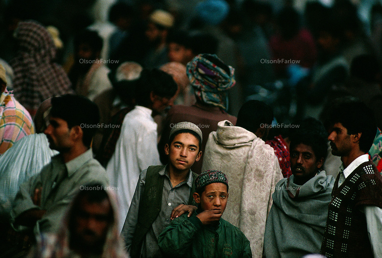 Faces of young men in a crowd on the street.