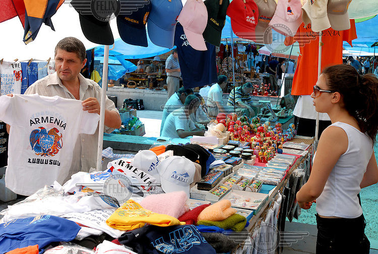 Vendor sells a patriotic t-shirt at a weekend street market in the centre of Yerevan.