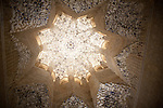 Illuminated view at night of richly decorated Islamic stonework ceiling Alhmabra palaces, Granada, Spain