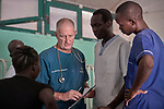 Dr. Clarke McIntosh, a pediatric pulmonologist from South Carolina in the United States, confers with others during rounds in the Mother of Mercy Hospital in Gidel, a village in the Nuba Mountains of Sudan. The area is controlled by the Sudan People's Liberation Movement-North, and frequently attacked by the military of Sudan. The Catholic hospital is the only referral hospital in the war-torn area.