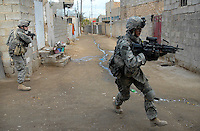 Soldiers from 1-37 Armor patrol the streets of south-central Ramadi in Anbar province, running across ally's to avoid frequent sniper fire from the upper levels of closely packed houses.